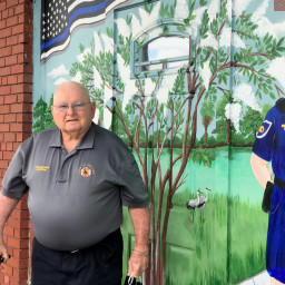 Mac McBride in front of his mural
